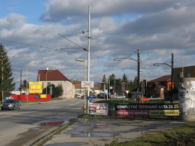 Nové a staré sloupy trakčního vědení u prejezdu silnice Trencin - Dubnica nad Váhom v Trencčanske Teplé